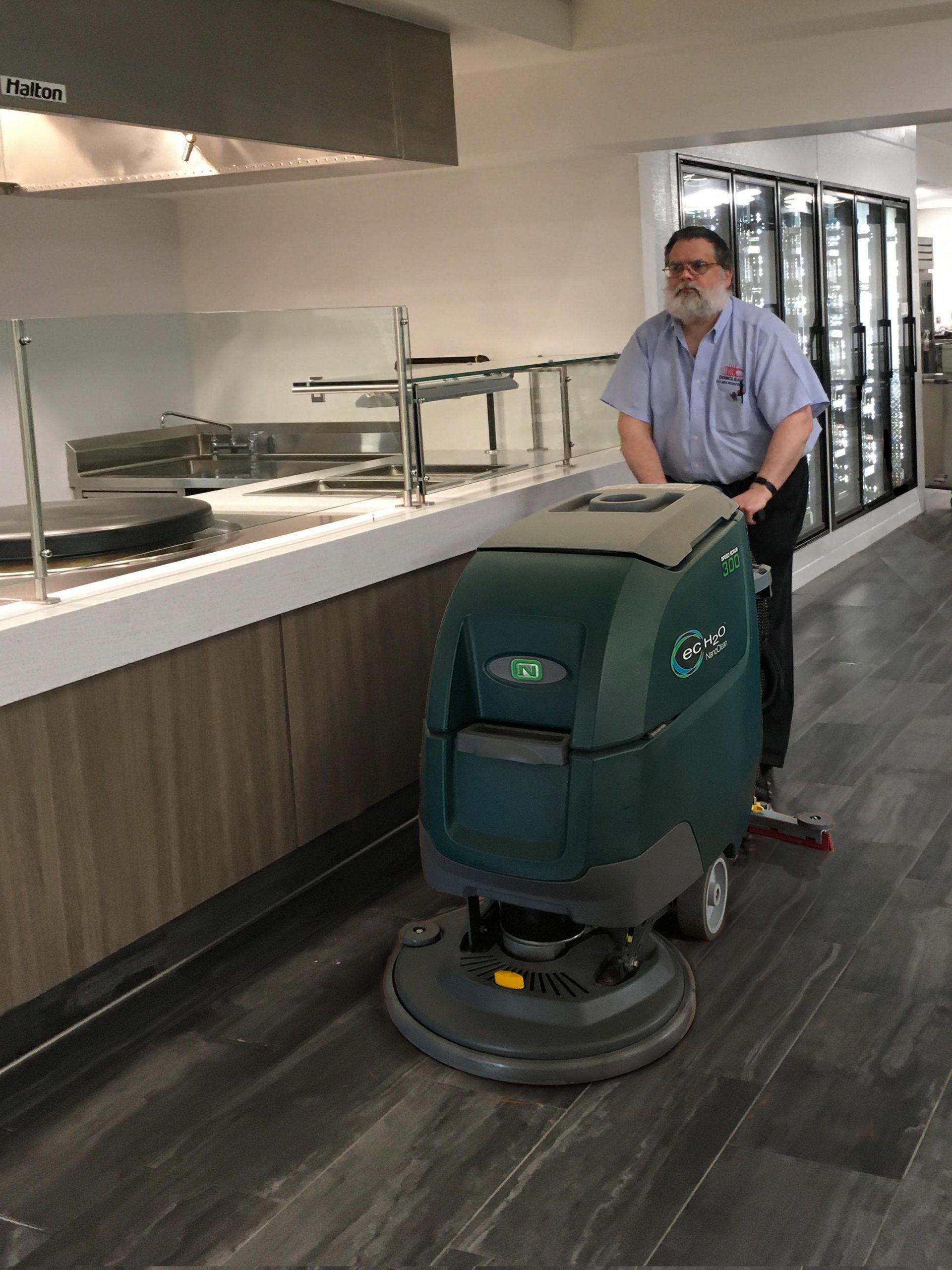 Man pushing floor cleaner through office hallway