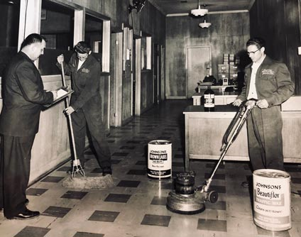 vintage photo of men cleaning a floor with a mop and an electric buffer