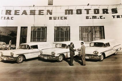 vintage photo of a car sales man at a dealership shaking another mans hand